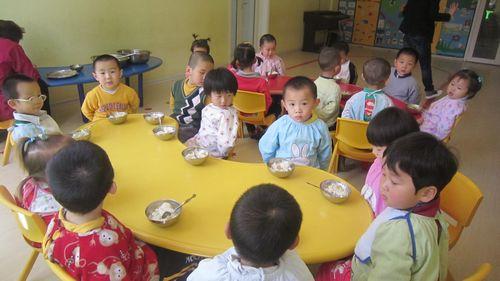 幼儿按顺序上桌吃饭,教师进行餐前教育,鼓励幼儿不挑食,不掉米粒