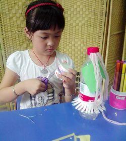 孩子们利用事先准备好的材料,如:一次性纸杯,矿泉水瓶子,毛线等.图片