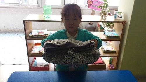 有的还边叠衣服边说儿歌,大部分孩子都把衣服叠得有模有样了.