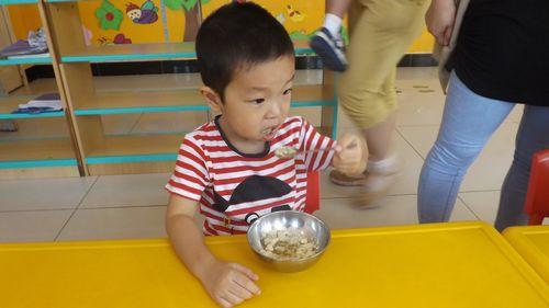 """看着小朋友可以自己拿着勺子吃饭,而且吃的那么高兴,老师想说:""""孩子们"""