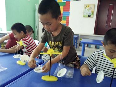幼儿们用最快的速度制作好天平后,用自己的方法比较物体的轻重.